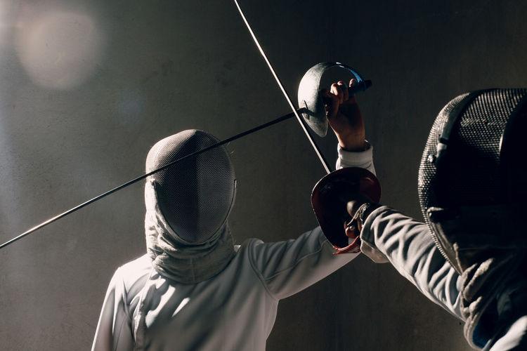 Close-up of men using sword