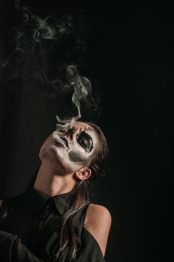 Portrait of young woman with face paint smoking against black background