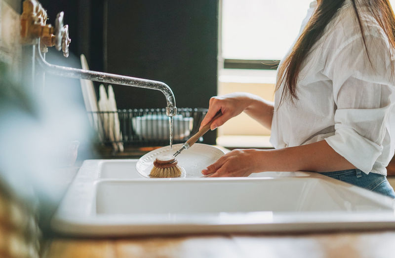 Midsection of woman cleaning dishes at home