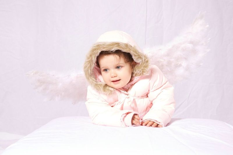 Cute baby girl with angel wings against pink background