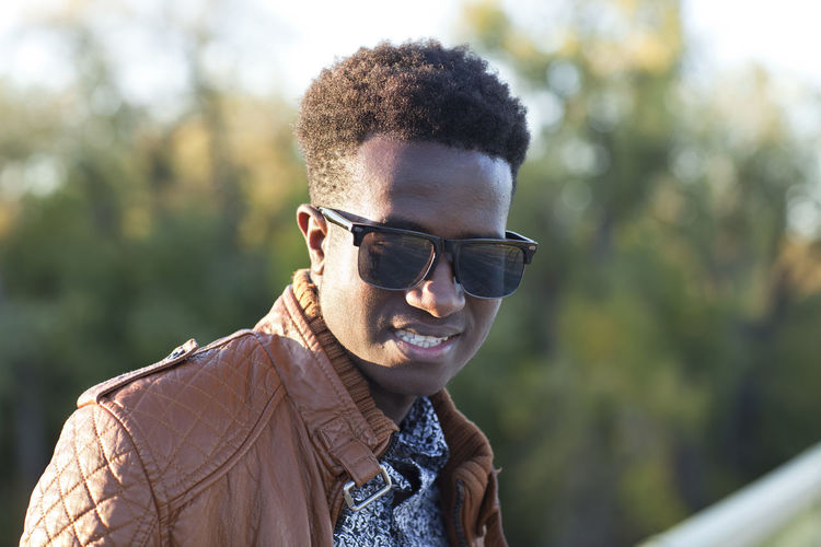 Handsome young black man with sunglasses and a leather jacket African American Autumn Leather Looking Down Sunlight Young Black Confident  Fall Focus On Foreground Handsome Jacket Kenyan Milennial One Person Outdoors Selective Focus Smiling Sunglasses Young Adult