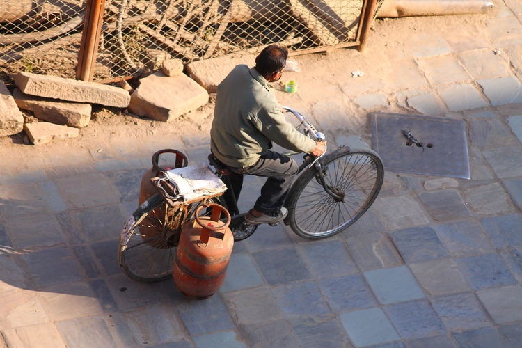 High angle view of man carrying gas cylinders on bicycle