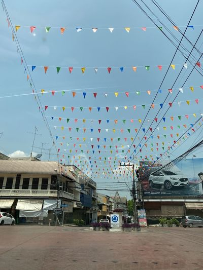 Multi colored flags hanging against sky