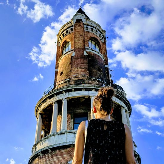 Woman looks at the tower Serbia EyeEm Selects Young Adult Zemun Belgrade Woman Back Sky Architecture Cloud - Sky Building Exterior Statue Civilization Female Likeness Sculpted Sculpture Historic Place Of Worship