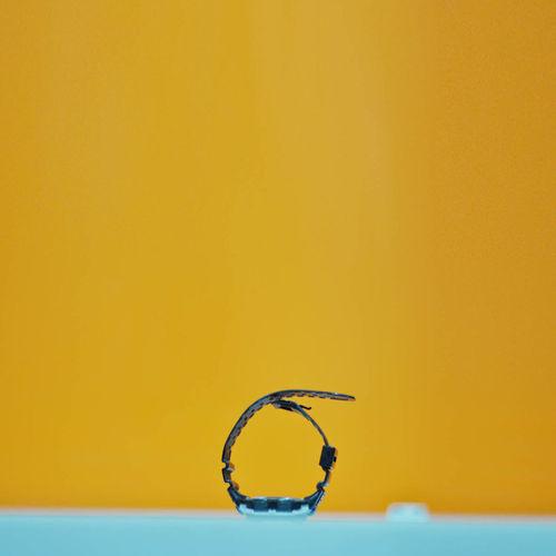 Close-Up Of Wristwatch Against Orange Background