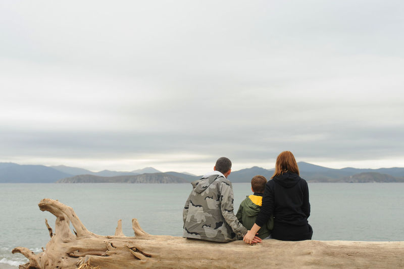 Family of three sits back old tree  on sandy beach and admires the blue clear sea and mountains