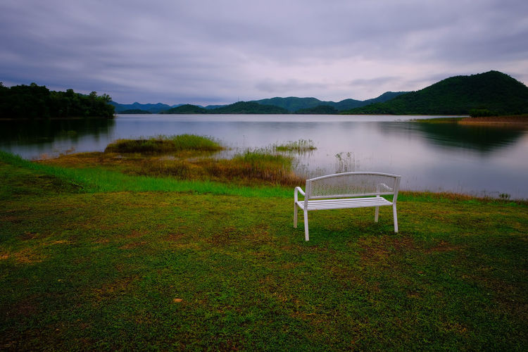 Empty chairs by lake against sky