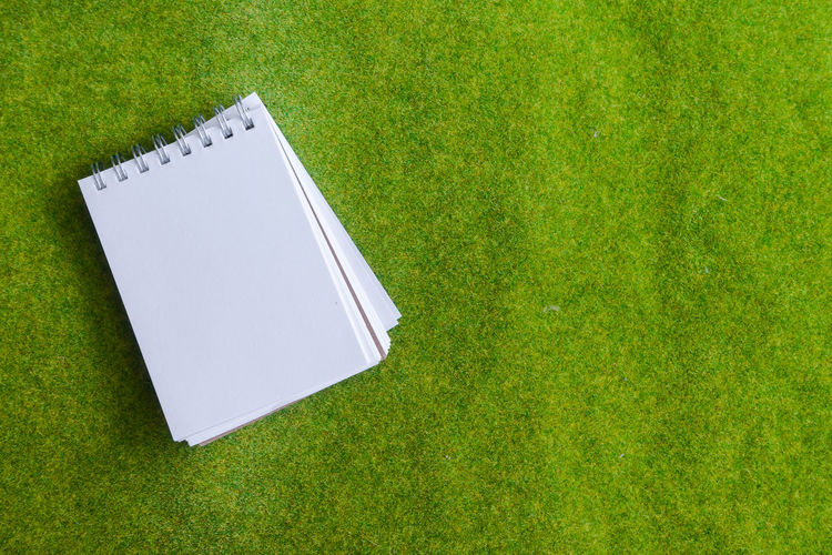 Directly Above Shot Of Spiral Notebook On Grass
