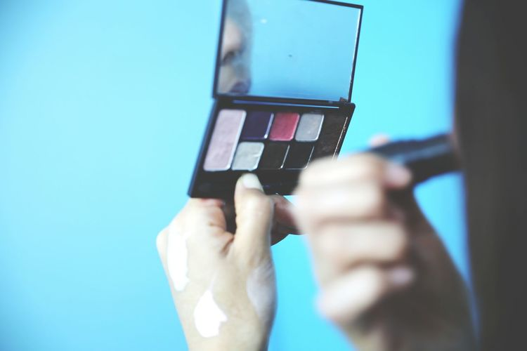 Cropped image of woman applying make-up
