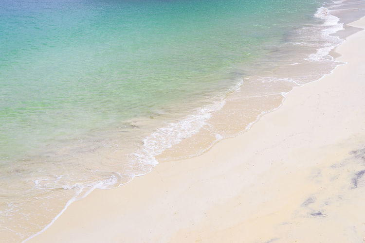 Soft Wave Of Blue Ocean On Sandy Beach. Background. Selective focus. Background Bay Beach Break Brown Caribbean Clear Coast Colorful Day Exotic Foam Golden Horizon Idyllic Marine Natural Nobody Ocean Outdoor Paradise Peace Reflection Relax Scenery Sea Seashore Seaside Season  Shiny Shore Sun Sunlight Sunny Sunset Sunshine Texture Thailand Tide Tourism Tranquil Travel Tropic Tropical Warm Water Wave Weather White Yellow