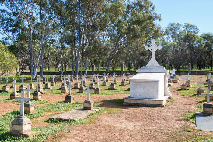 White tomb surrounded by rows of headstones in New Norcia Cemetery in New Norcia, Western Australia. Australia Burial Ground Cemetery Cross Gravestones Graveyard Greenery Headstones Landscape Memorial Nature New Norcia Peaceful Religious  Rememberance Rest In Peace Resting Place Rows Of Things Spiritual Symbolic  Tomb Tranquility Trees Western White
