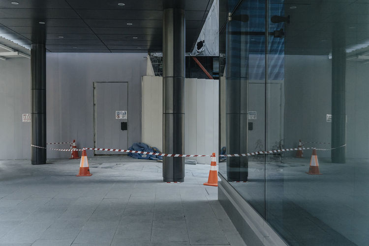 Traffic Cones With Tape And Column By Closed Door In Room