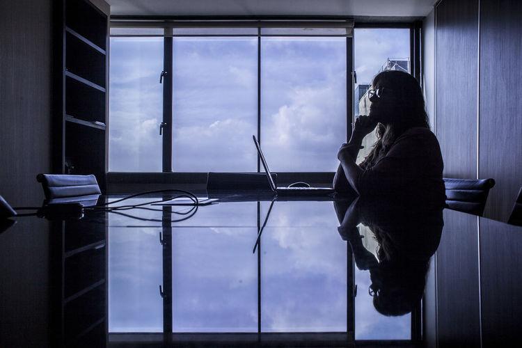 Reflection of woman sitting on glass window