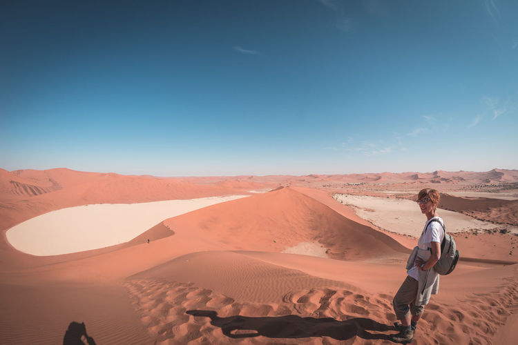 Portrait of female tourist standing at namib desert in naukluft national park during sunny day