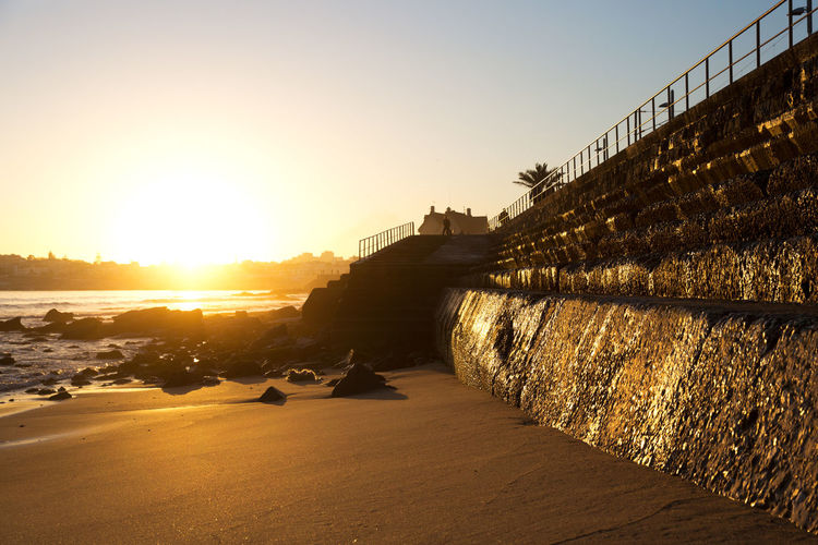 Holiday Portugal Railing Sunlight Sunset_collection Backlit Beach Beach Promenade Blue Sky Evening Illumination Masonry Rocks And Water Sand Sea Seaside Sunset Village Warm