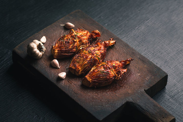High angle view of chicken meat with garlic cloves served on wooden tray
