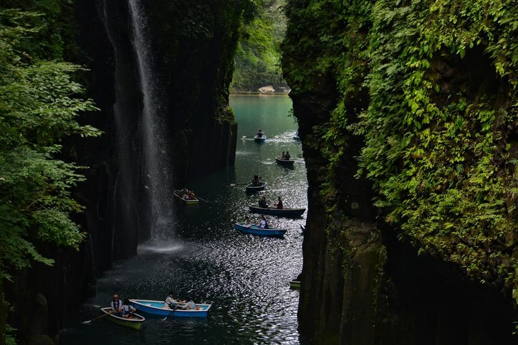 People Boating By Waterfall Amidst Rock Formations
