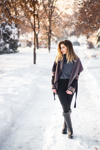 Full length portrait of young woman walking in winter