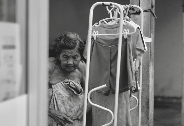 Close-Up Of Senior Woman Wrapped In Towel Standing By Rack