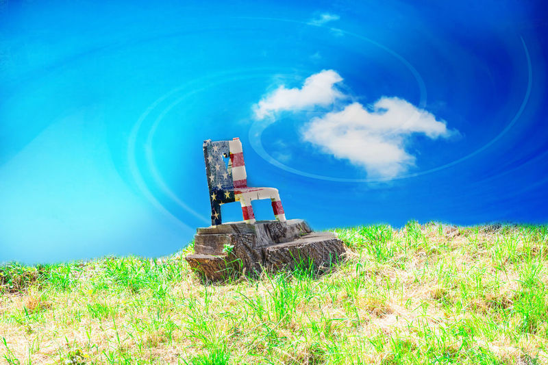 chair on a lawn in Stars and Stripes colors against dramatic sky. American Flag ; Furniture; Usa Blue Carved Wooden Figure Cloud - Sky Day Dramatic Sky; Drilling Rig Field Grass Industry Nature No People Oil Industry Oil Pump Oil Well Outdoors Piece Of Furniture; Sky Technology Wood Chair