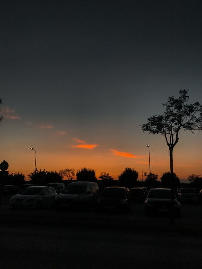 Cars on street against sky at sunset