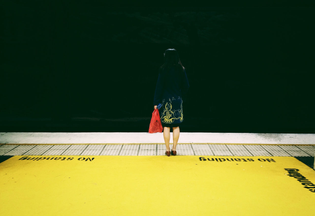 Woman waiting at railroad station