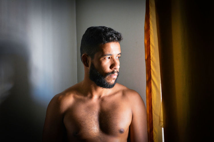 Portrait of shirtless man looking away while standing against wall