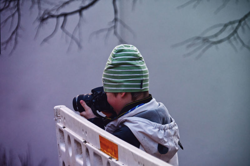Portrait of child takin pictures with dslr camera