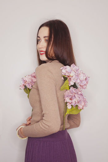 Beautiful woman with flowers against colored background