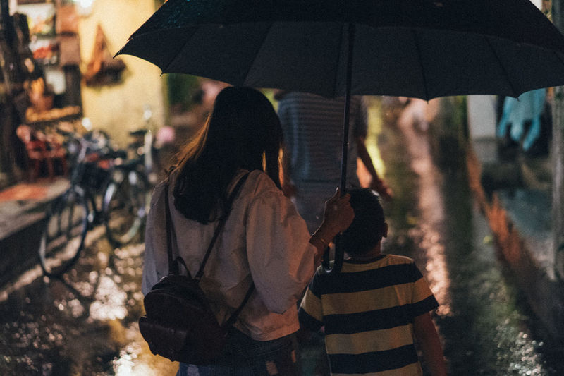 Hoi an by night with family Kids Childhood Child Night Nightphotography Streetphotography Street Street Photography Men Women Light And Shadow Light Lighting Equipment Walking Walking Around Playing Rain Raining Real People Rear View