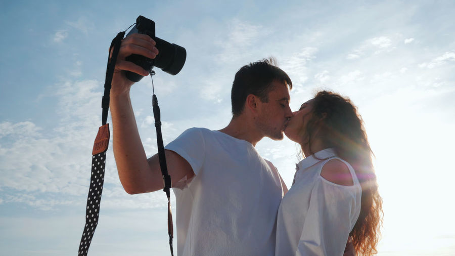 Young Couple Kissing On Mouth Against Sky During Sunny Day