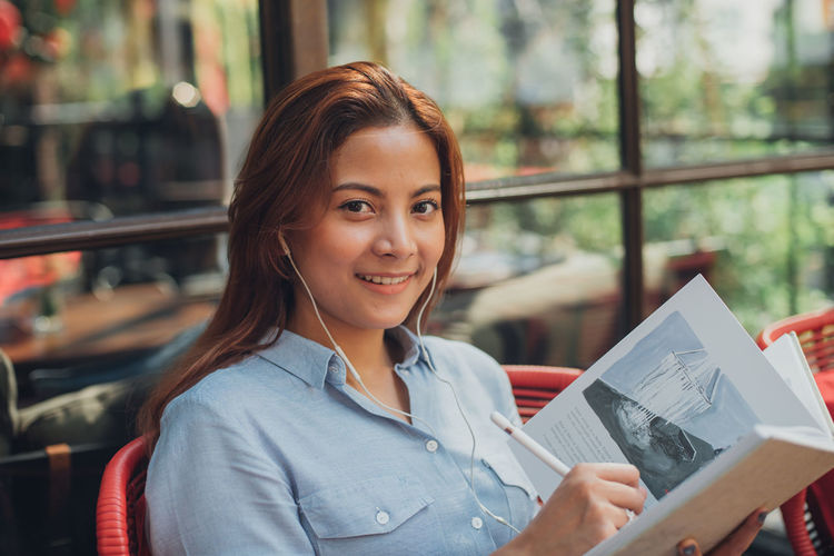 Portrait Of Smiling Young Woman Writing In Book At Cafe
