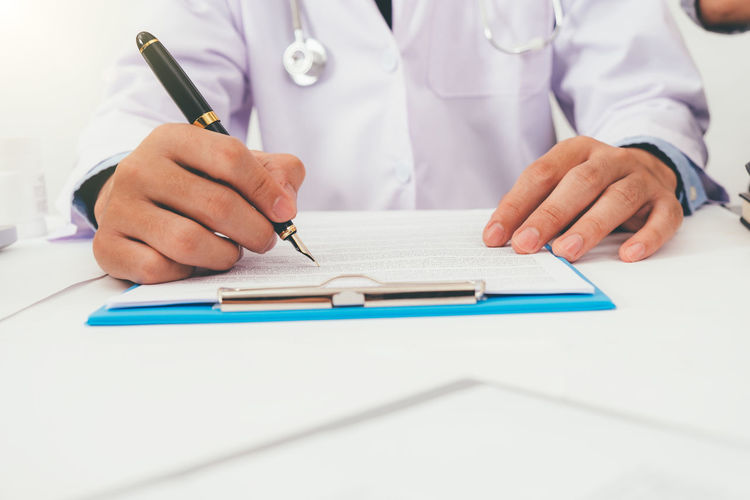 Midsection of doctor writing medical report in hospital