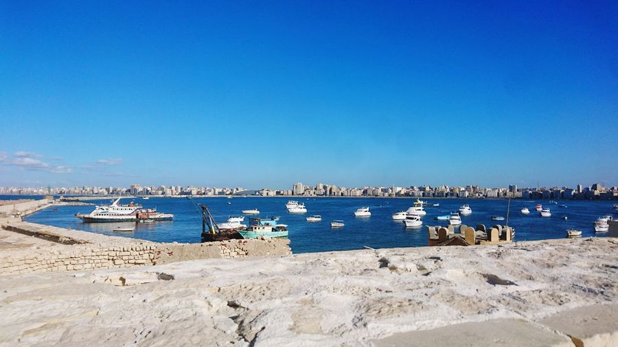 EyeEmNewHere No People Outdoors Sky Water Sea Alexandria Egypt Skyline Boats⛵️ Clear Sky Sunlight Daylight Mediterranean Sea Fishing Boats View Eastern Harbour Qayetbay Citadel Alexandrian Landmark Beauty In Nature Beautiful Alexandria Escaping From The Crouds