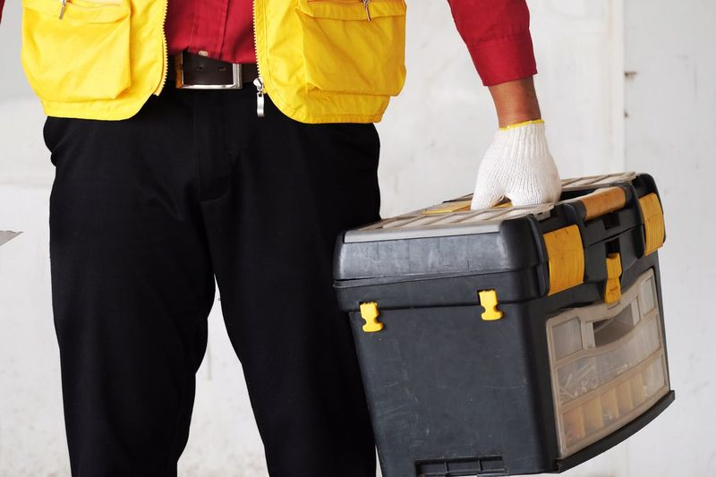 Midsection of carpenter holding toolbox against wall