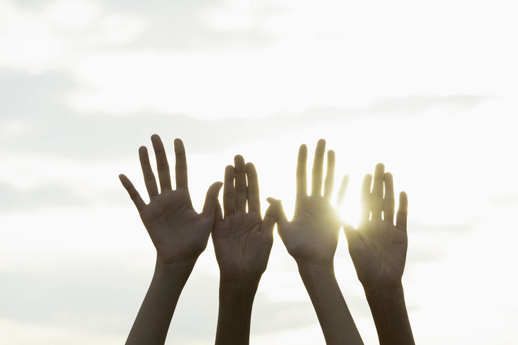 Cropped hands of people against sky