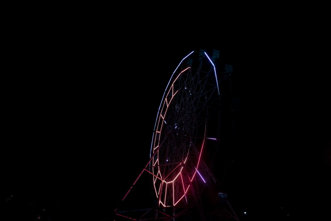 LOW ANGLE VIEW OF ILLUMINATED FERRIS WHEEL AGAINST BLACK SKY