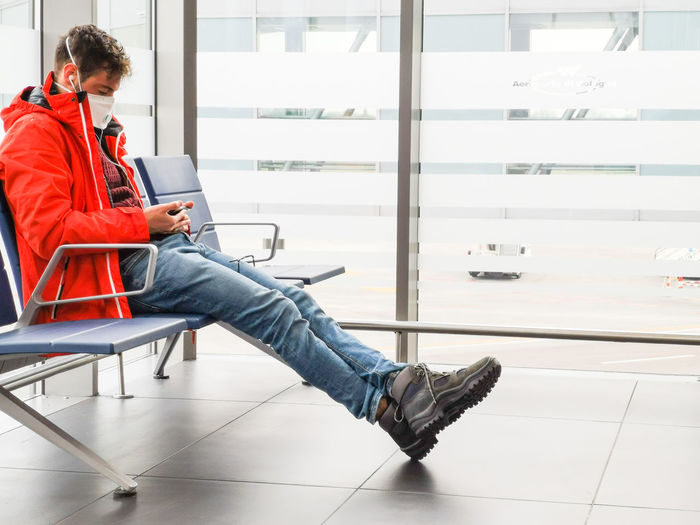 Full length of young man wearing mask sitting on airport