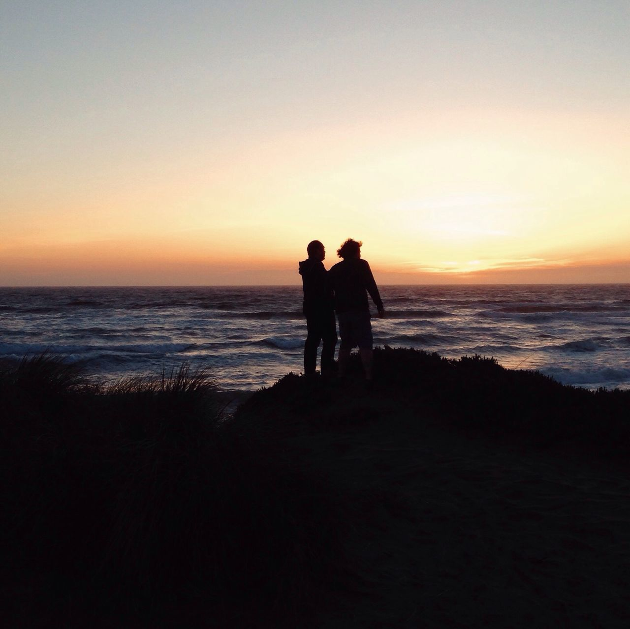 sunset, sea, beach, silhouette, nature, togetherness, beauty in nature, horizon over water, water, two people, shore, sky, scenics, love, tranquil scene, leisure activity, men, real people, friendship, tranquility, standing, outdoors, vacations, full length, lifestyles, sand, bonding, women, wave, day, adult, people