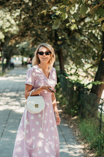 Portrait of happy young woman wearing sunglasses standing on footpath