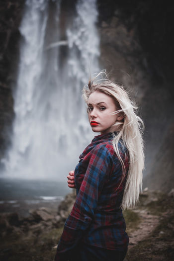 Portrait of beautiful young woman standing against waterfall