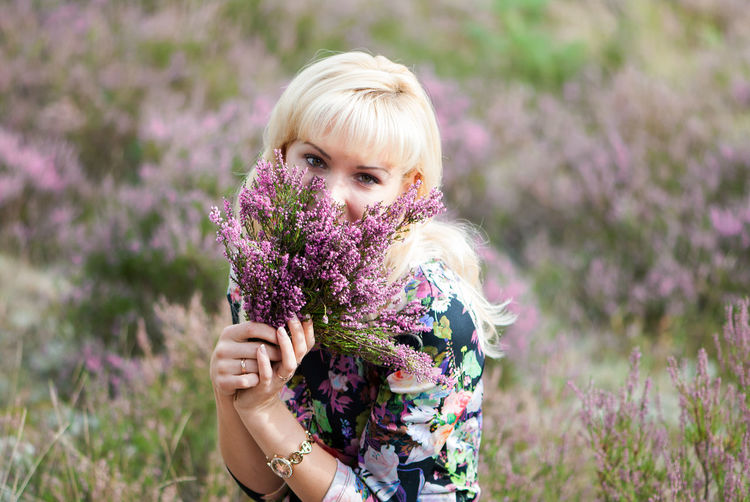 beautiful woman in blooming heather field Beautiful Woman Beauty In Nature Blond Hair Flower Flower Head Focus On Foreground Fragility Freshness Front View Growth Heathers Holding Lavender Leisure Activity Lifestyles Nature One Person One Young Woman Only Outdoors Plant Purple Real People Wildflower Young Adult Young Women