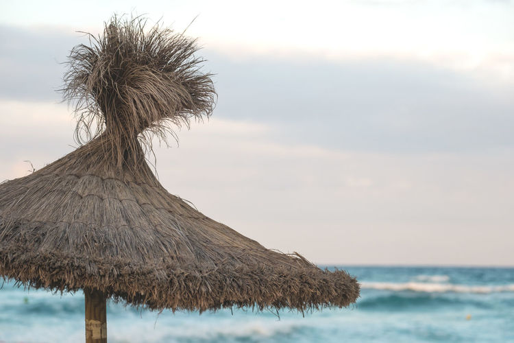 Thatched roof at beach against sky