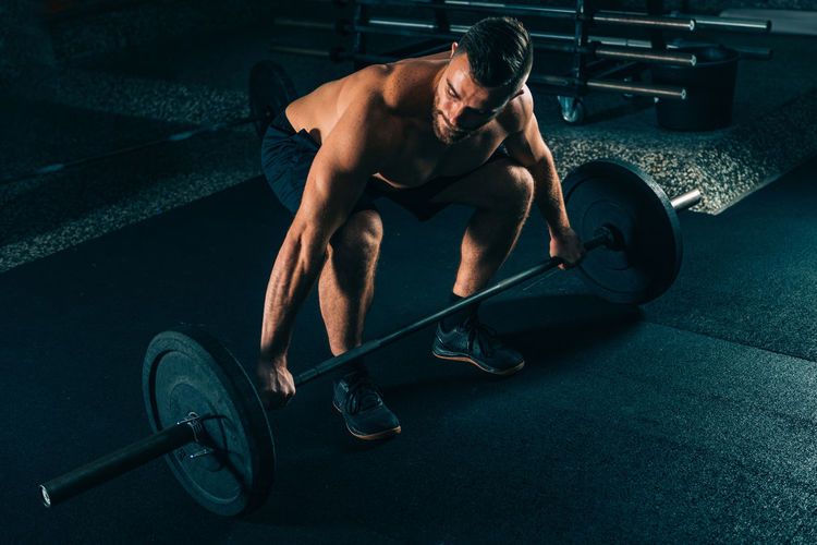 Male Athlete Exercising With Barbell In Gym