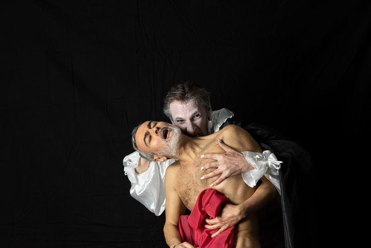 Couple kissing against black background