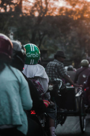 Grab Helmet Grab Adult City Clothing Communication Day Evening Evening Sky Focus On Foreground Government Group Of People Headwear Helmet Men Outdoors People Portrait Real People Rear View Standing Street Sun Sunset Transportation Uniform