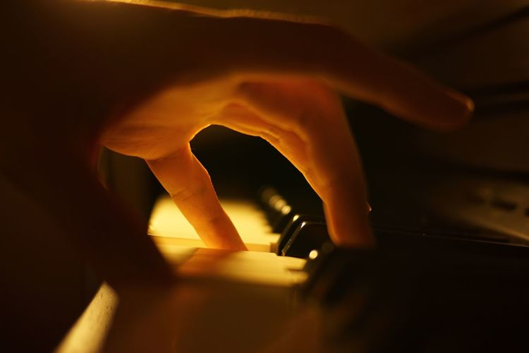 Close-Up Of Human Hand Playing Piano