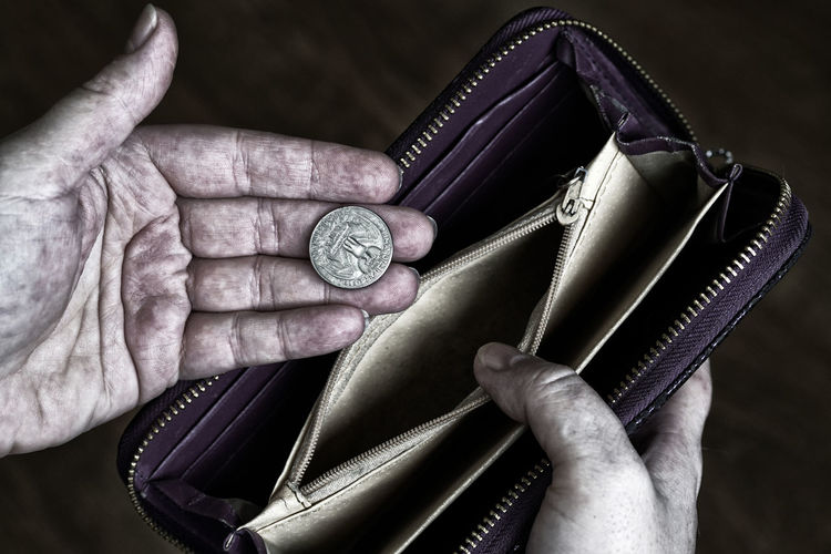 Cropped hands of woman holding purse with coin