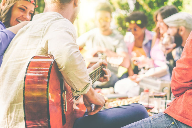 Happy friends playing guitar at picnic People Picnic Garden Happy Friends Smiling Laughing Group Of People Young Adult Youth Playing Guitar Men Arts Culture And Entertainment Music Musical Instrument Adult Crowd Leisure Activity Day Group Women Lifestyles Event Togetherness