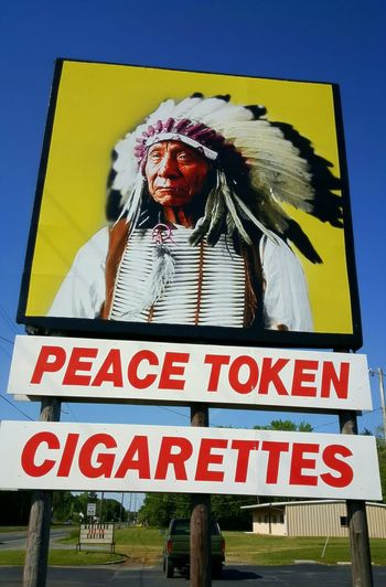 Tobacconists. InternationalDayofPeace Text Billboard Advertisement Figure Roadside Shot Signs Signage Native American Red & Yellow Roadside America Road Travel Photography Low Angle Of View Blue Sky EyeEm Gallery Eyeemphotography EyeEm Best Shots S6